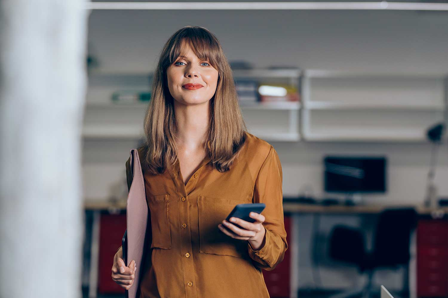 Woman in office holding phone and looking ahead